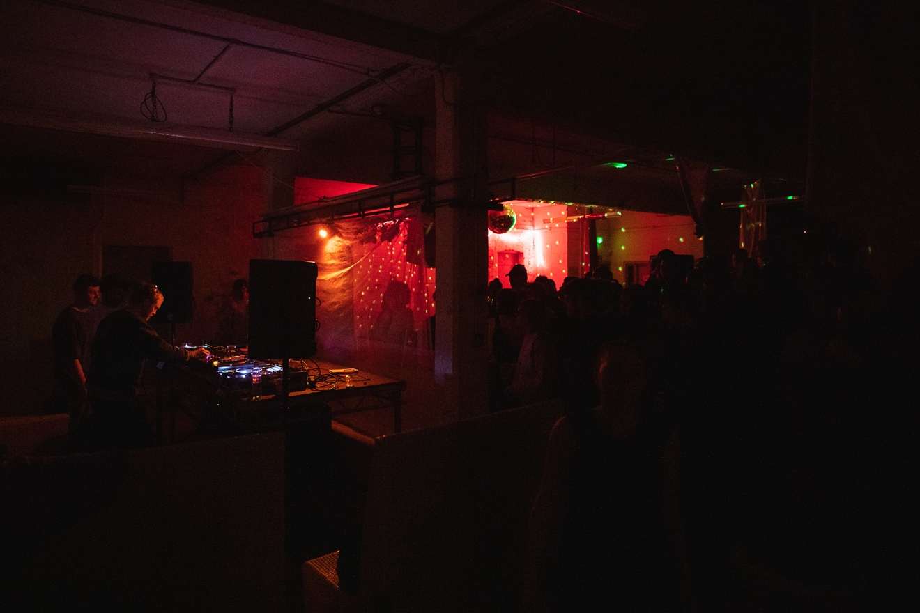 Dark room with red lights and disco ball. A DJ is playing to the shadows of dancers on a crowded dance floor.