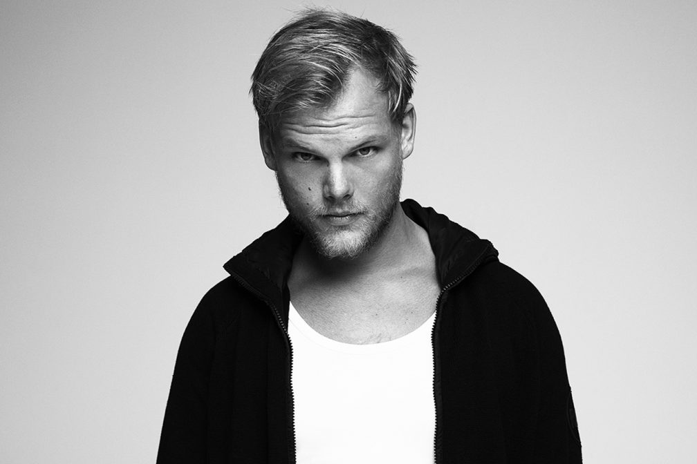 Avicii is wearing a white t-shirt and a black hoodie